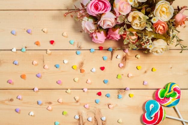 Fiori di rose con caramelle a forma di cuore su fondo in legno tono di colore pastello