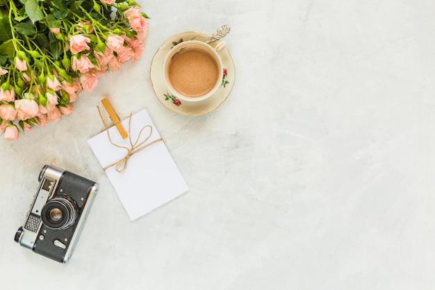 Fiori di rose con tazza di caffè; biglietto di auguri e macchina fotografica d'epoca su sfondo concreto