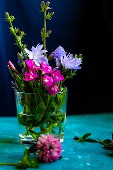 Fiori di trifoglio rosa sul tavolo con sfondo blu