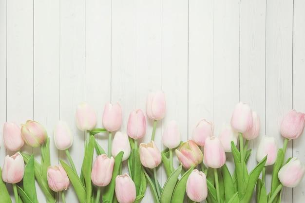Fiori di tulipani rosa chiaro su fondo in legno chiaro.