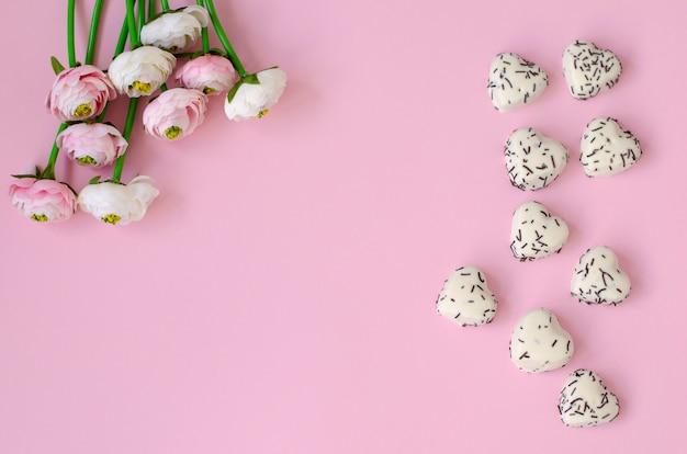 Fiori e biscotti a forma di cuore su sfondo rosa pastello.