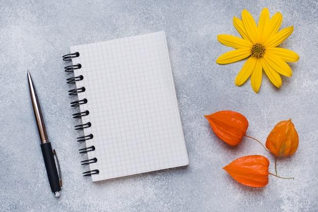 Fiori e blocco note di autunno per testo sulla tavola con lo spazio della copia