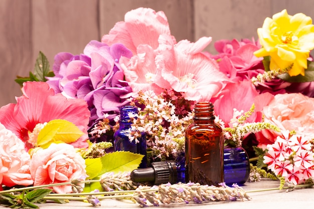 Fiori e bottiglie di olii essenziali per aromaterapia
