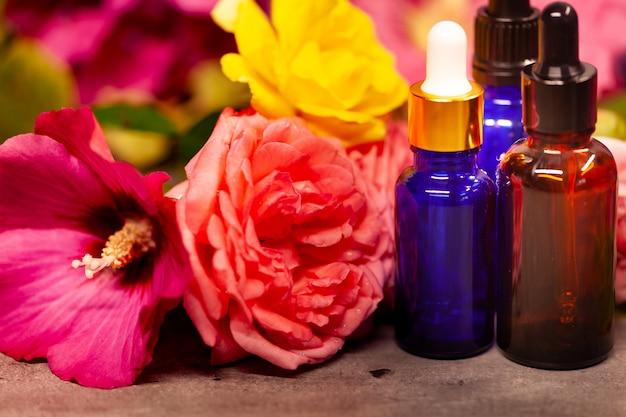 Fiori e bottiglie di olii essenziali per l'aromaterapia