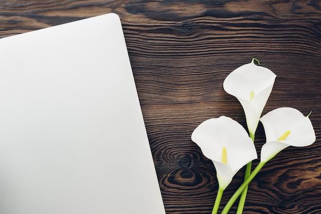 Fiori e computer portatile bianchi piani della calla su legno, vista superiore.