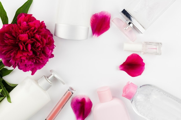 Fiori e flaconi per la cosmetica che incorniciano lo spazio circolare