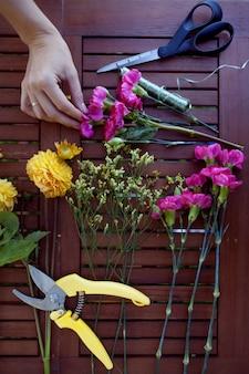 Fiori e strumenti sul tavolo, posto di lavoro del fiorista, vista superiore di natura morta