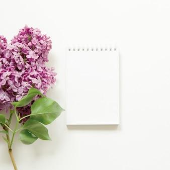 Fiori e taccuino lilla. fiori di primavera. vista dall'alto, disteso, copia spazio.