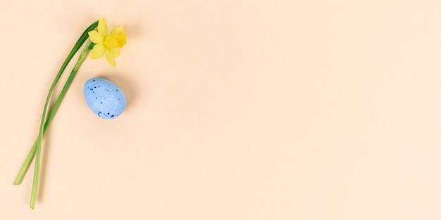 Fiori e uova di pasqua gialli sul rosa