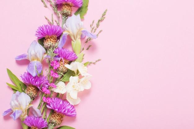Fiori estivi sulla superficie della carta rosa