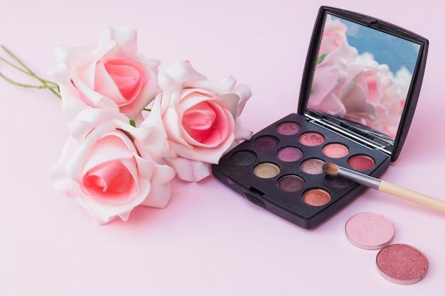 Fiori finti rosa con palette fard e ombretto con pennello per il trucco
