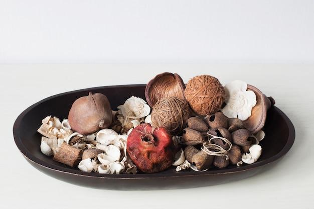 Fiori, foglie e frutti asciutti su un piatto di legno sulla tavola bianca