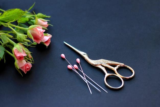 Fiori, forbici per cucire e perni su uno sfondo scuro il concetto di congratulazioni per la vacanza e il ricamo