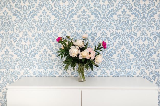 Fiori freschi del taglio delle peonie in vaso con lo spazio della copia sulla tavola bianca sul blu