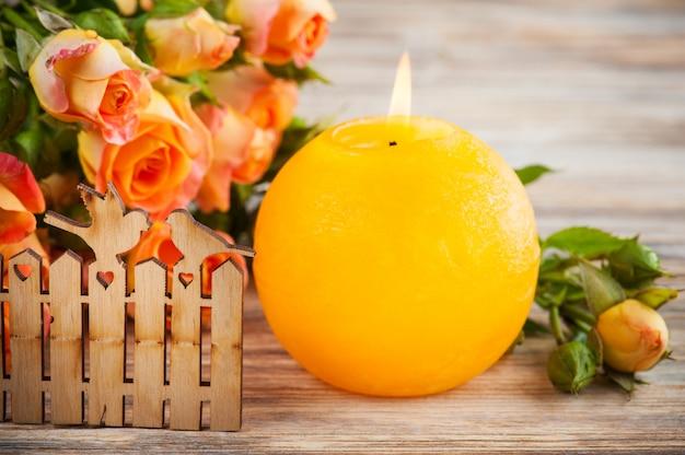 Fiori freschi delle rose arancio, uccelli e candela accesa