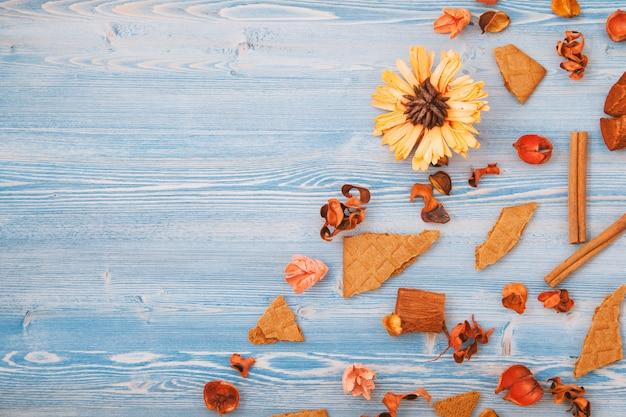 Fiori gialli e rossi asciutti di autunno su un di legno blu