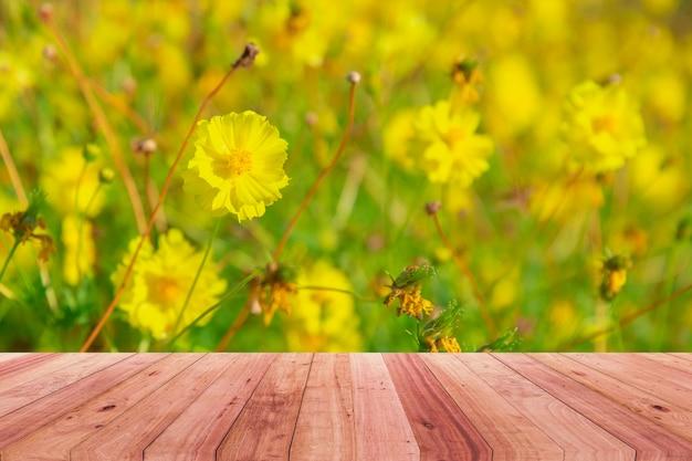 Fiori gialli su fondo di legno dell'annata, progettazione del confine.