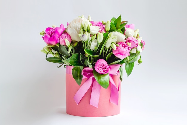 Fiori in una scatola di cappello. bouquet di peonie rosa e bianche, eustoma, spray rose in una scatola rosa