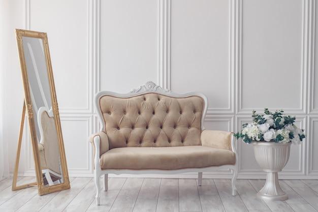 Fiori in vaso accanto al divano bianco. minimalismo.