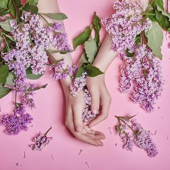 Fiori lilla delle donne cosmetiche naturali della mano di modo