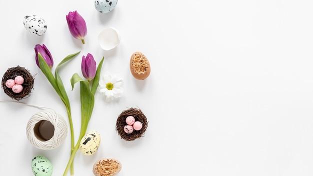 Fiori piatti distesi e cesto con uova