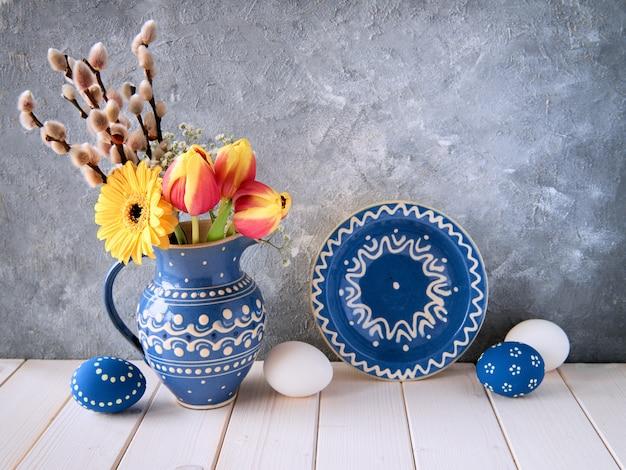 Fiori primaverili in brocca in ceramica blu con placca abbinata e uova pasquali su grigio