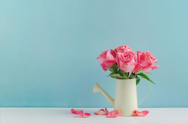 Fiori rosa appassiti all'annaffiatoio su fondo di legno bianco e blu