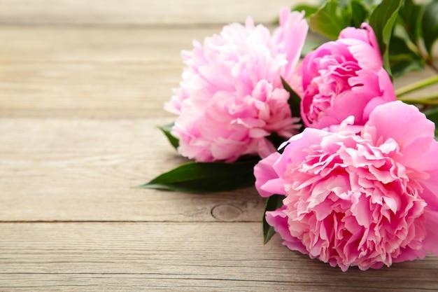 Fiori rosa della peonia su fondo di legno grigio.