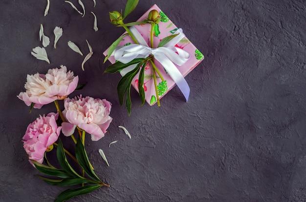 Fiori rosa della peonia su fondo di pietra grigio. il giorno della donna o lo sfondo del matrimonio. concetto di san valentino