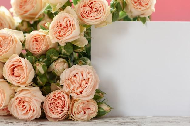 Fiori rosa delle rose con la carta di regalo sul rosa