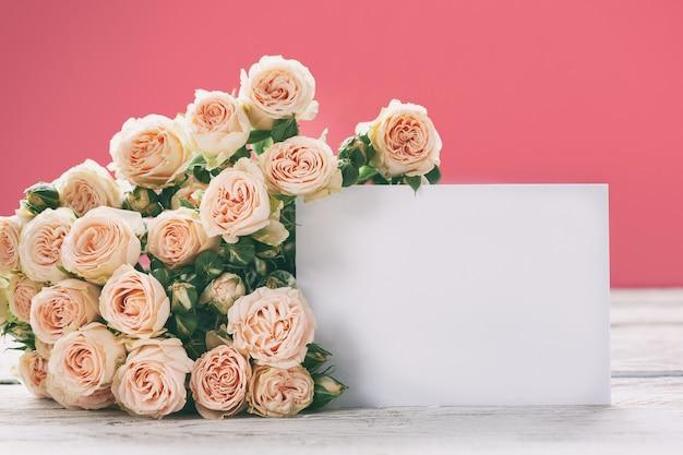 Fiori rosa delle rose con la cartolina d'auguri in bianco