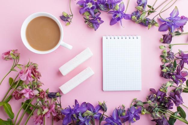 Fiori rosa e viola di colombina e una tazza di caffè con il taccuino sul rosa pastello.