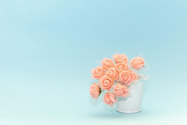 Fiori rosa in un secchio bianco giocattolo su uno sfondo azzurro, fiori per la vacanza