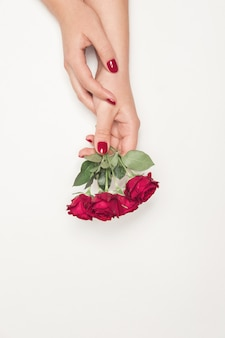 Fiori rose nelle mani della ragazza, vista dall'alto, roselline rosse