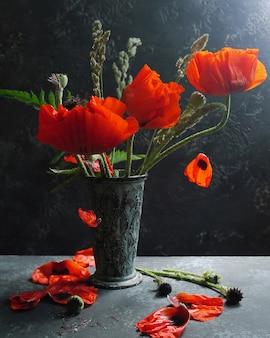 Fiori rossi del papavero in vaso d'epoca. petali volanti