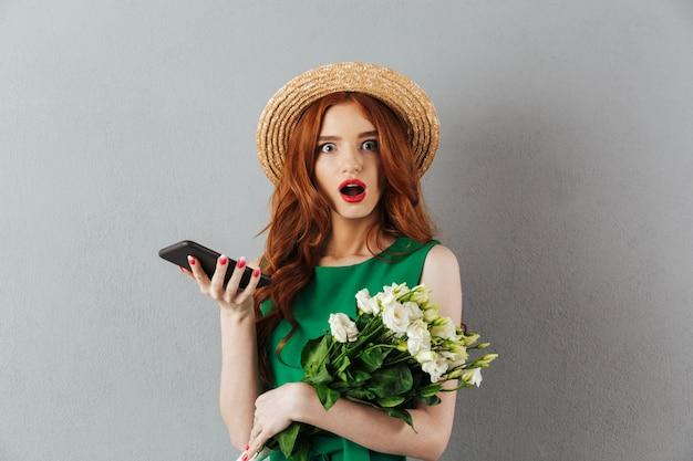 Fiori rossi scioccati giovani della donna che chiacchierano dal telefono.