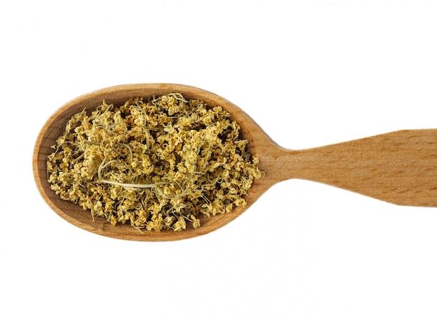 Fiori secchi di sambuco in un cucchiaio di legno su uno sfondo bianco.
