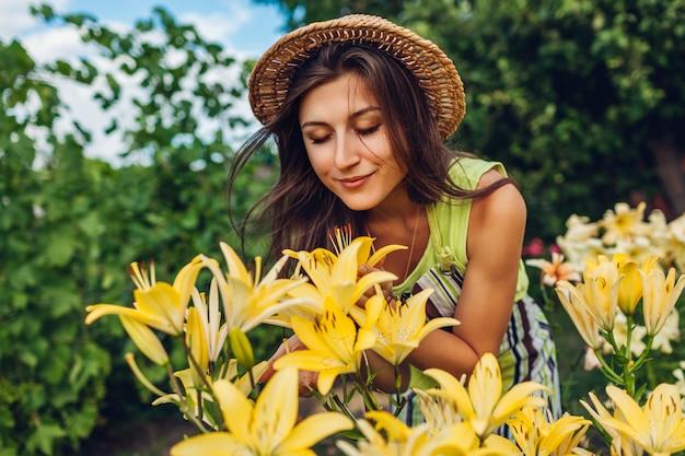 Fiori sententi l'odore della giovane donna in giardino. giardiniere prendersi cura dei gigli. concetto di giardinaggio