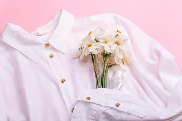 Fiori stagionali in un bouquet minimalista nelle mani di una camicia bianca