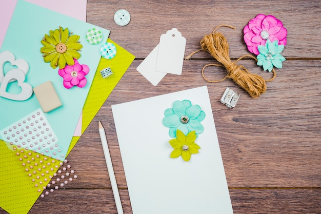 Fiori su carta bianca con matita; tag; fiore e corda sullo scrittorio di legno