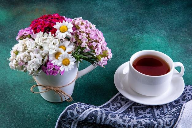 Fiori variopinti di vista laterale in una tazza con una tazza di tè sull'asciugamano di cucina su verde