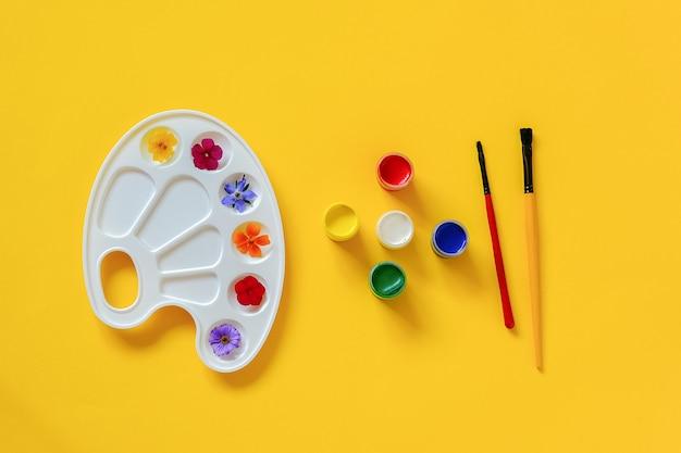 Fiori variopinti sulla tavolozza artistica, spazzola, gouache su fondo giallo, spazio della copia.