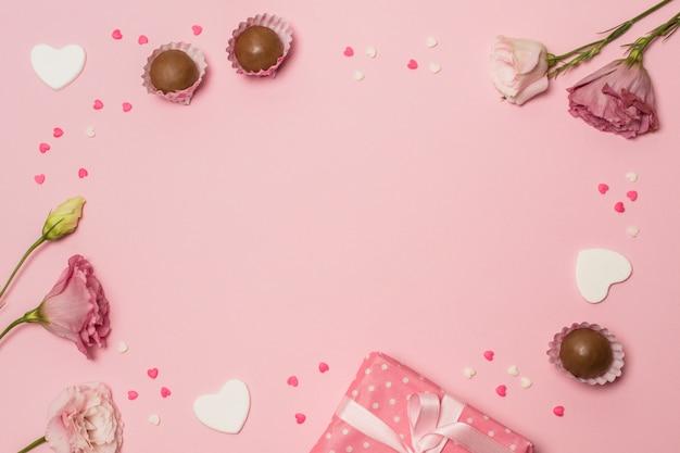 Fiori vicino a confezioni regalo e caramelle di cioccolato
