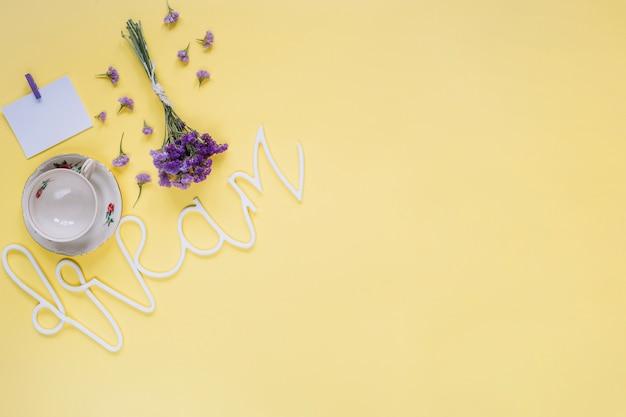 Fiori viola con la parola da sogno e tazza vuota sulla superficie gialla