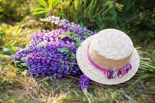 Fiori viola del lupino coperti di cappello di paglia nel campo. il cappello vicino ad un mazzo di lupino fiorisce sull'erba di mattina. picnic estivi di concetto. cappello di paglia decorato con fiori bouquet. decorazioni per la casa in stile rustico
