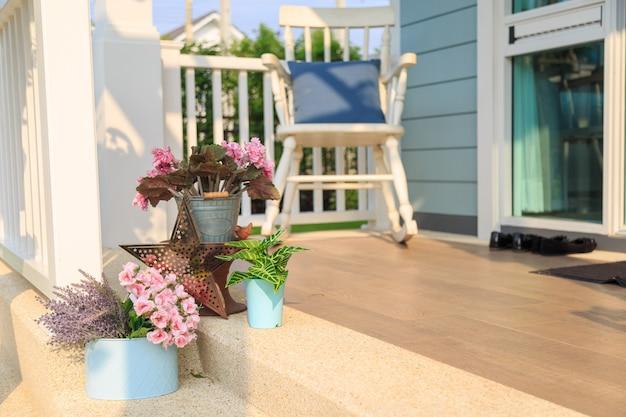 Fiorisca il mazzo su un pavimento con fondo della sedia di oscillazione in un balcone