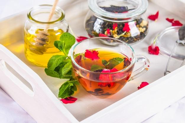 Fiorisca il tè in una tazza, un barattolo di miele, tè in un barattolo, su un vassoio bianco a letto.