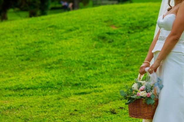 Fiorisca la ragazza alle nozze che tengono un cestino dei fiori.
