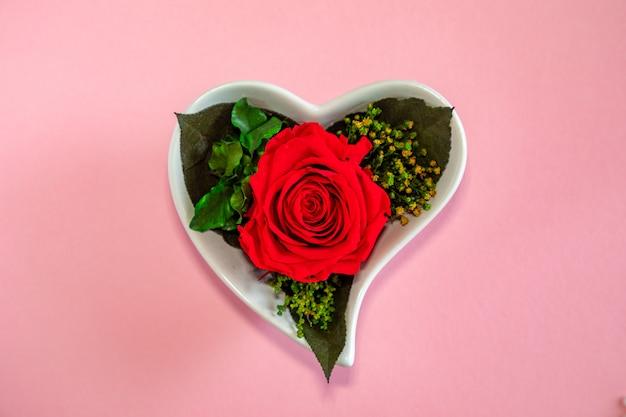 Fiorisca la rosa rossa in un vaso in forma di cuore su un fondo rosa, vista superiore