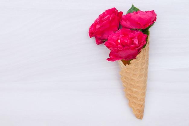 Fiorisce le rose rosse in un cono della cialda su fondo di legno bianco. vista piana, vista dall'alto, sfondo floreale.